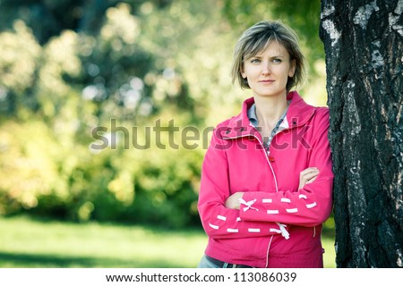 Young woman outdoors in fall clothing with autumn natural surroundings leaning on the tree stem, with copy space - stock photo