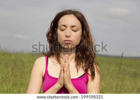 Young woman outdoors in green fields doing meditation in namaste pose - stock photo
