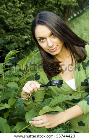 Young woman outdoors looking through a magnifying glass on the green leaves of the tree