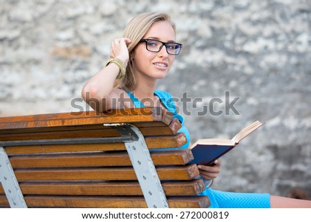 Young woman outdoors sitting on the bench and reading a book, with eyeglasses, dressed in blue dress. - stock photo