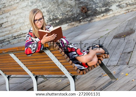 Young woman outdoors sitting on the bench and reading a book, with eyeglasses, in colorful coat. - stock photo