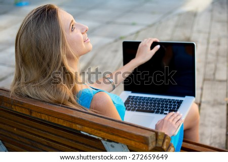Young woman outdoors sitting on the bench with notebook.