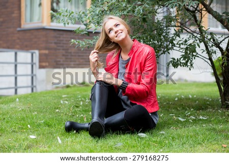 Young woman outdoors sitting on the grass and looking to the sky. - stock photo