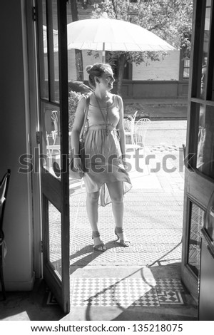 Young woman outside a restaurant, black and white - stock photo