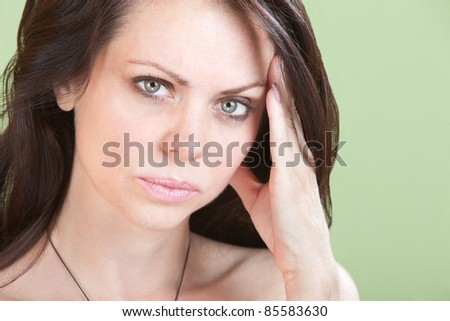 Young woman over green background holds side of her head. - stock photo