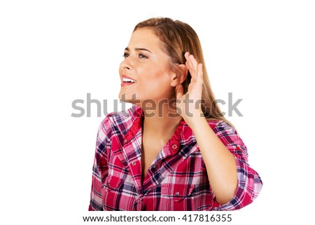 Young woman overhearing a conversation - stock photo