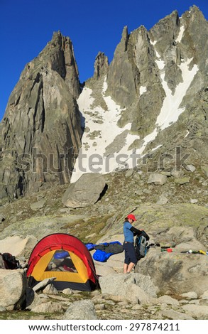 Young woman packing her backpack at a campsite with a red tunnel tent high in the beautiful mountains. - stock photo