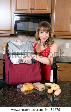 Young Woman Packing Picnic Hamper