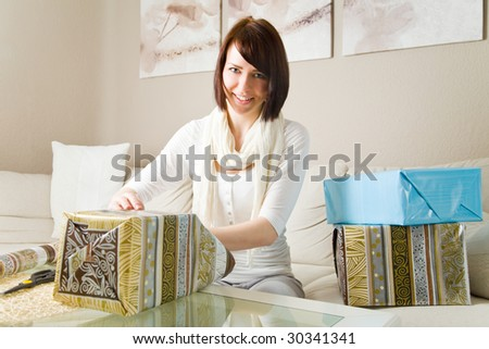 Young woman packing presents in her living room - stock photo
