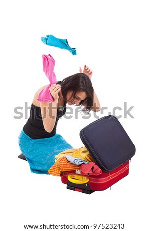 Young woman packing up her suitcase - stock photo