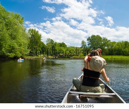 Young woman paddling on a gentle little river - stock photo