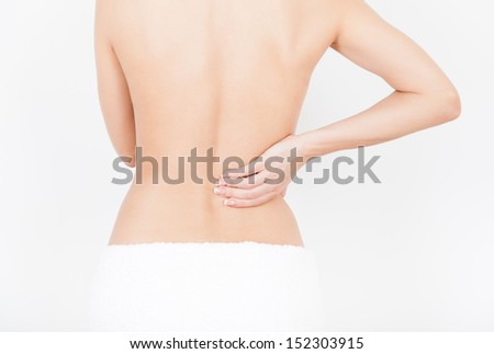 young woman pain in lower back, touch hand waist spine, backache body in white towel - stock photo