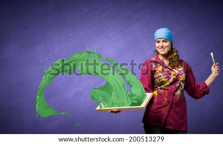 Young woman painter holding frame with colorful splashes