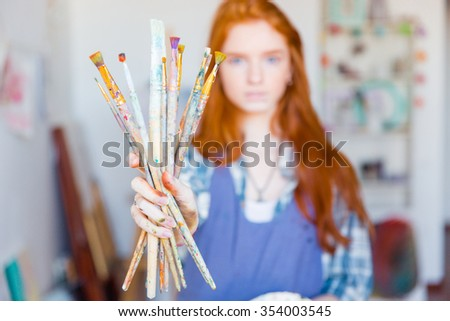 Young woman painter with long red hair in blue apron showing dirty paintbrushes in artist workshop - stock photo