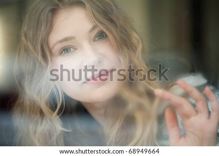 young woman painting a heart with her fingers on a window pane - stock photo