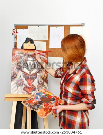 Young woman painting a picture on the canvas in his studio. The artist paints near an easel with a picture. - stock photo