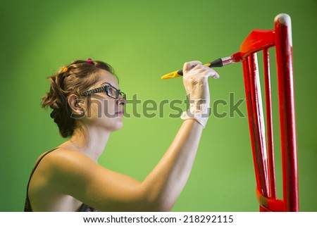 young woman painting a red chair on green background - stock photo