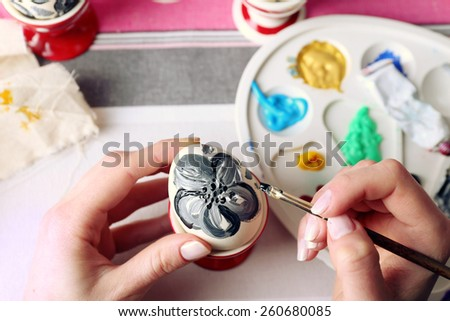 Young woman painting Easter eggs on table close up - stock photo