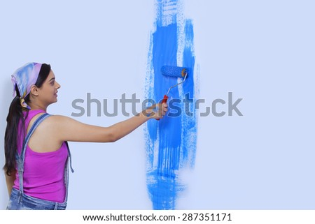 Young woman painting her home wall - stock photo