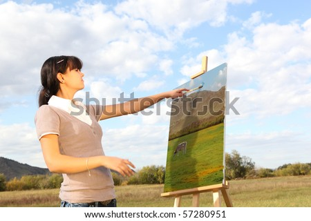 Young woman painting landscape - stock photo