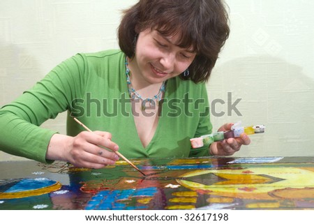 Young woman painting on the glass surface with vitrage dye
