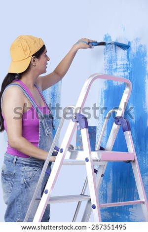 Young woman painting wall while standing on step ladder - stock photo