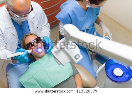 Young woman patient have dental surgery dentist use UV lamp - stock photo