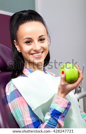 Young woman patient with perfect straight white teeth waiting for dentist in  chair and smiling with green apple in hand. Beautiful girl ready for dental checkup - stock photo
