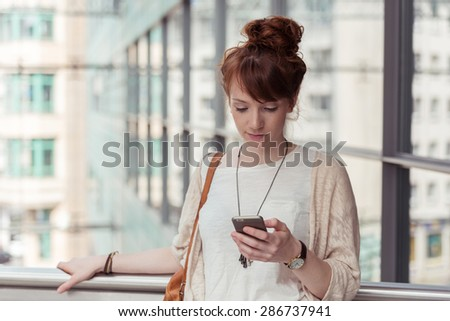 Young woman pausing to check an sms or text message on her mobile phone against a backdrop of high-rise urban buildings - stock photo