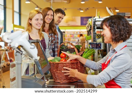 Young woman paying basket of groceries at supermarket checkout - stock photo