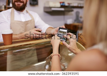 Young woman paying for coffee by credit card at coffee shop. Focus on woman hands entering security pin in credit card reader. - stock photo