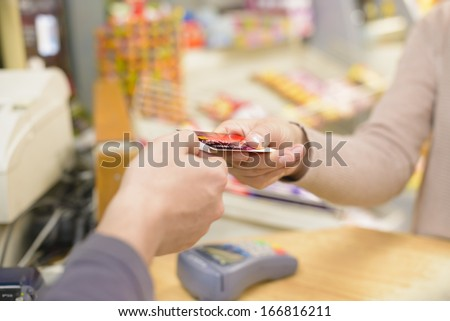 Young woman paying in a shop - stock photo