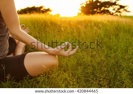 Young woman peacefully meditating in a open field. - stock photo