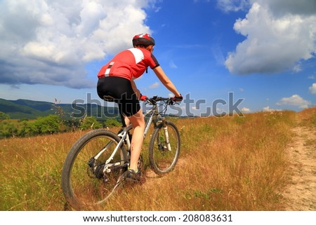 Young woman pedaling on grass covered trail
