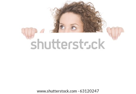 young woman peeking behind empty white billboard