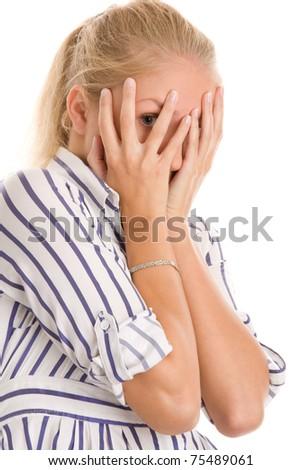 Young woman peeking through fingers - stock photo