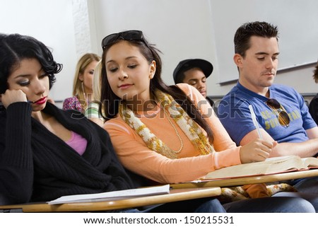 Young woman peeping into friend's notes during class lecture