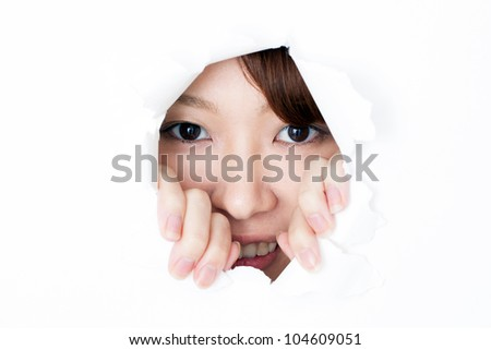 Young woman peeping through hole on paper - stock photo