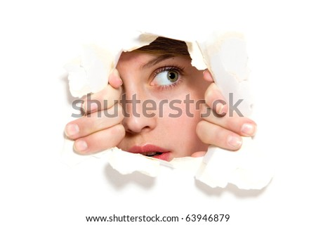 Young woman peeping through hole on paper