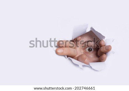 Young woman peeping through hole on paper. Selective focus on eye. - stock photo