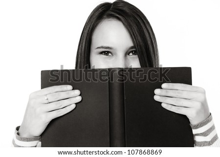 young woman peering over a hard back book - stock photo
