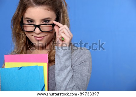 Young woman peering over her glasses - stock photo