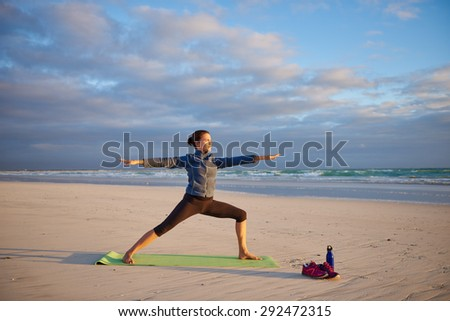 Young woman performing a yoga pose on the beach with morning sun shining on her - stock photo