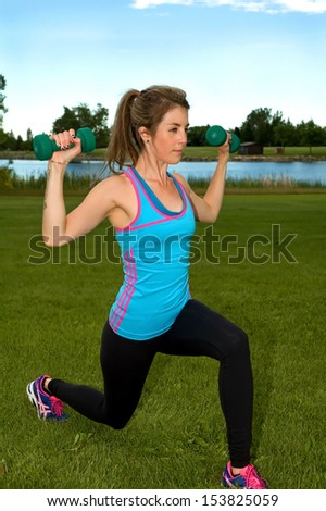 Young woman performing compound exercise, consisting of lunge and shoulder press.
