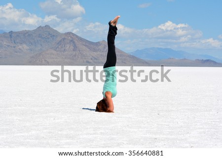 Young woman performing head stand yoga pose on the Bonneville Salt Flats in Utah. - stock photo