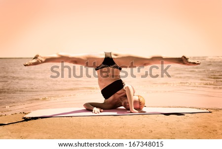 Young woman performing splits while standing on hands and shoulders at the beach - stock photo