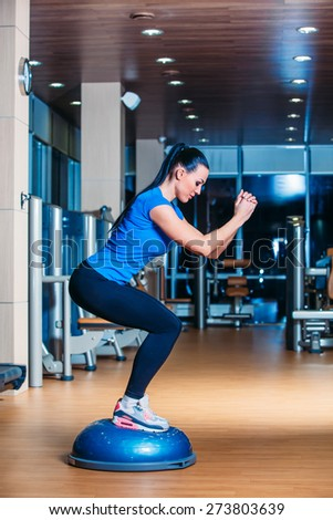 Young woman performing Step aerobics exercises in the gym - stock photo