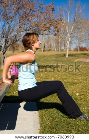 Young woman performing tricep dips on a bench. - stock photo