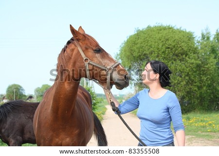 Young woman petting chestnut horse - stock photo