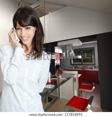 Young woman phoning at home, by the kitchen - stock photo